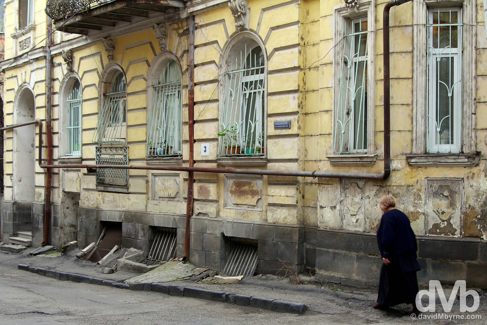 Walking past a dilapidated building in the Old Town of Tbilisi, Georgia. March 19, 2015.