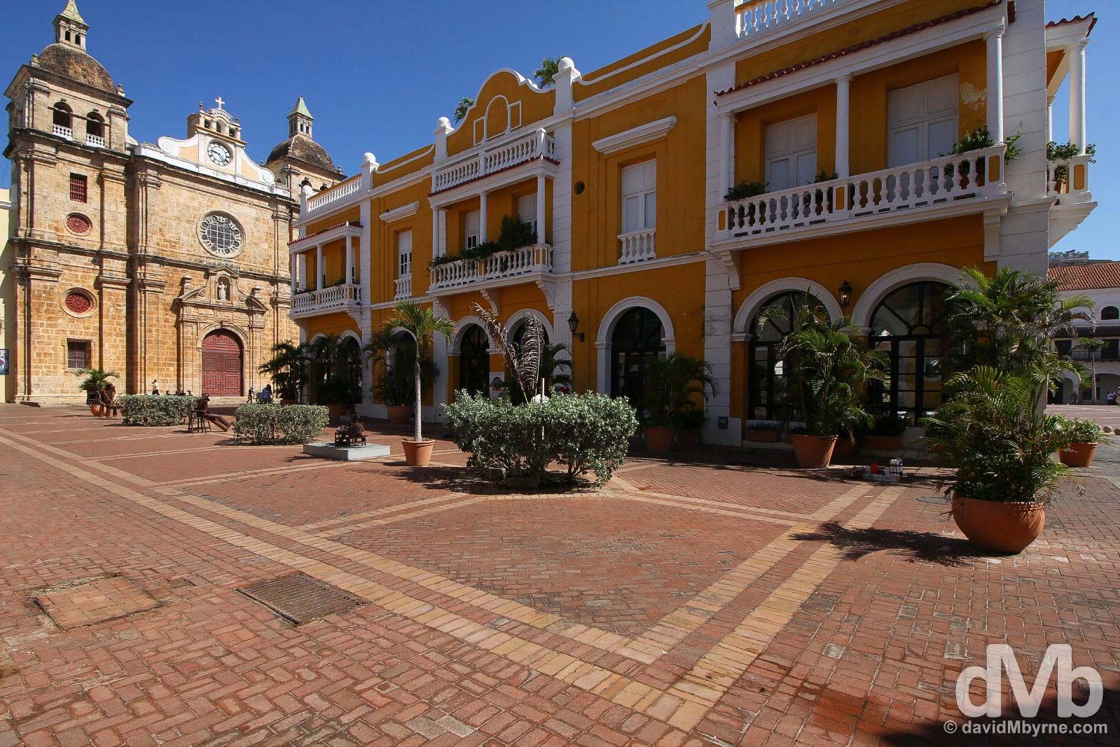 Colonial buildings, including the facade of Iglesia de San Pedro Claver, as seen from the corner of Plaza de la Aduana in Old Town Cartagena, Colombia. June 25, 2015.