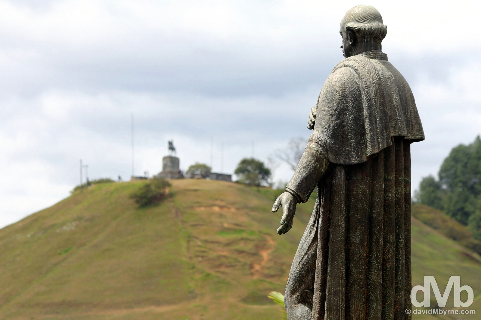 A statue of Guillermo Valencia in the grounds of the Museo Guillermo Valencia with the city lookout of El Morro de Tulcan in the distance. Popayan, Colombia. June 30, 2015.