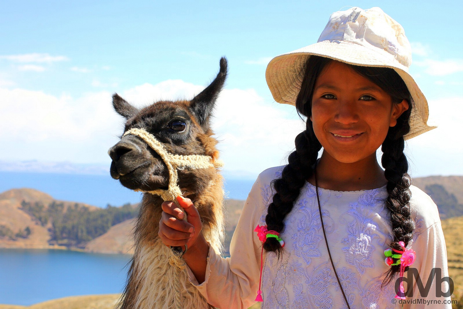 A girl with a llama on the path approaching the village of Yumani on Isla del Sol in Lake Titicaca, Bolivia. August 24, 2015.