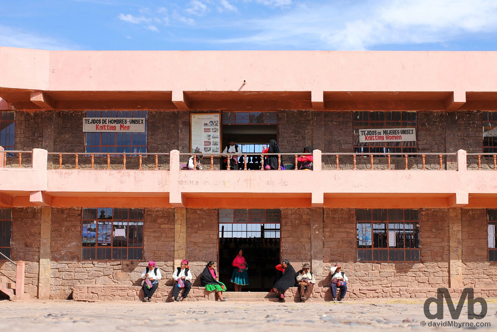 Locals sitting outside a weaving market in the main square of Taquile Island, Lake Titicaca, Peru. August 20, 2015.