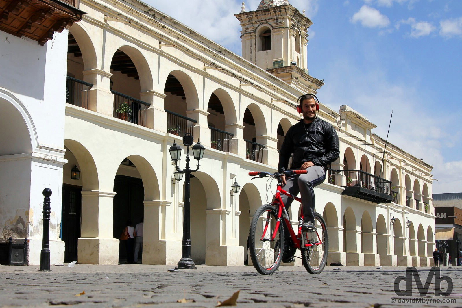 Smiles cycling past the Cabildo on Plaza 9 de Julio, Salta, northern Argentina. September 7, 2015.