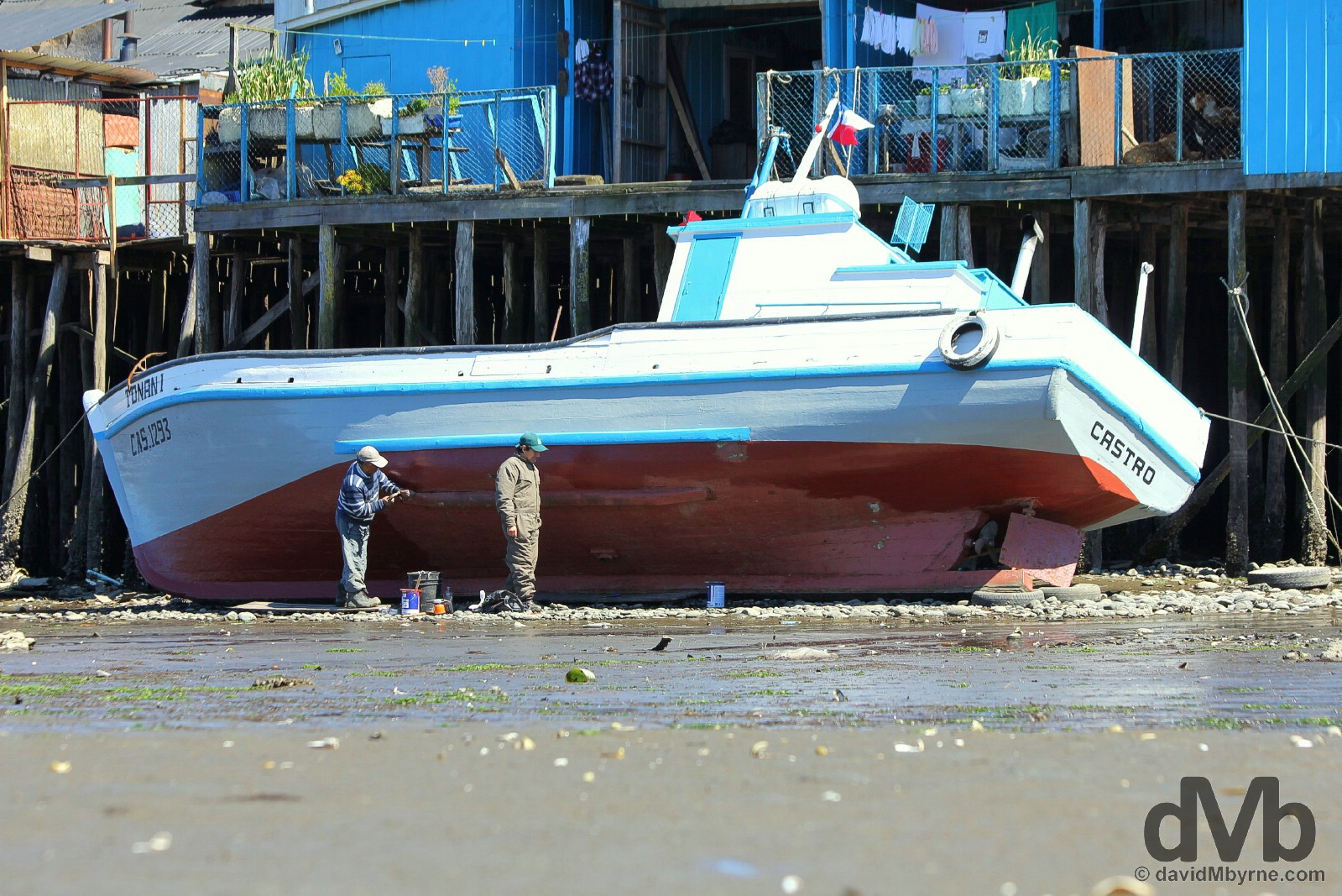 Boat maintenance at low tide in Castro, Chiloe, Chile. October 22, 2015.