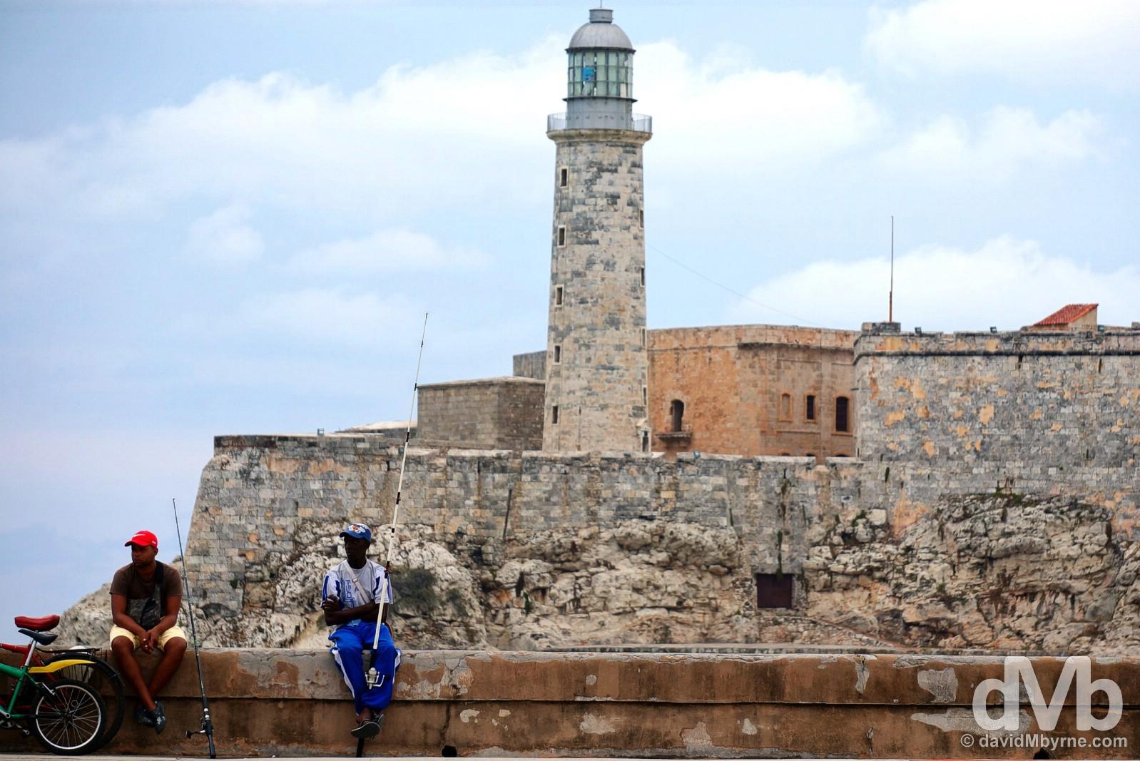 Sitting on the walls of the Malecon fronting Castillo de San Salvador de la Punta in Havana, Cuba. April 30, 2015.