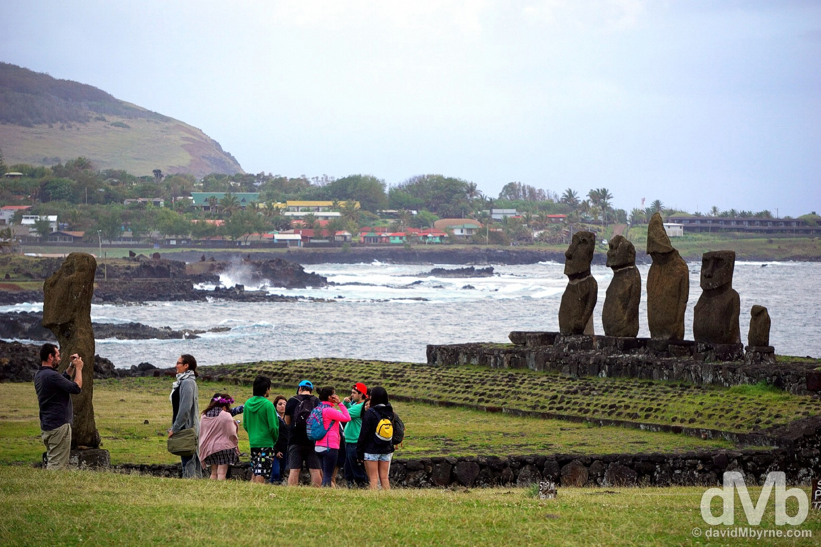 Approaching the end of Day 1 at Tahai on the outskirts of Hanga Roa with the slopes of the island's Rano Kau volcano (see Day 2) in the distance. This image shows the (mostly badly eroded) moai of the two other Tahai ahu - the lone moai of Ahu Tahai itself (left) & the 5 moai of Ahu Vai Uri (right). Easter Island, Chile. September 27, 2015.