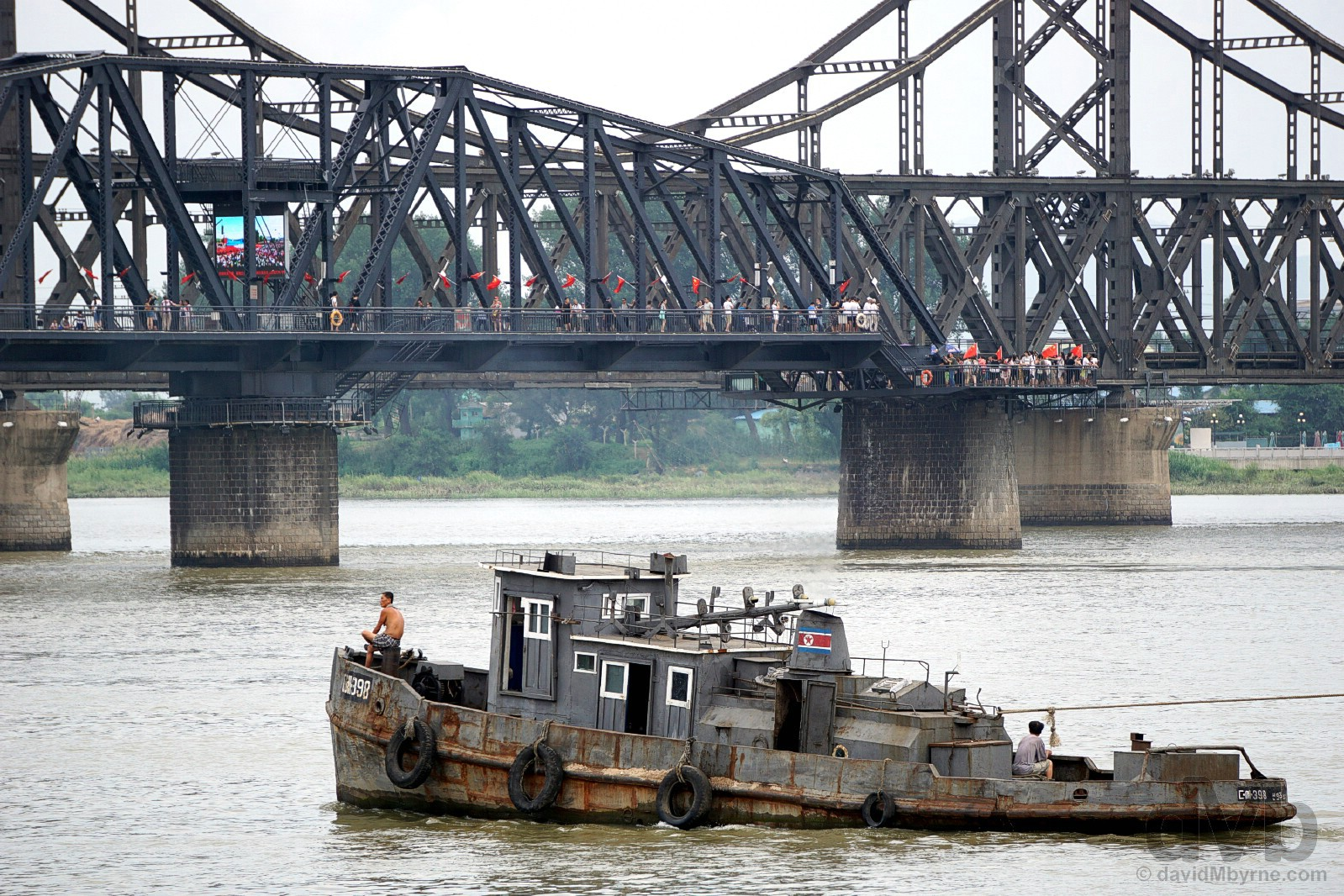 A North Korean-registered tug boat plies the Yalu River with the Broken Bridge in the background as seen from Dandong, Liaoning province, China. August 13, 2017.