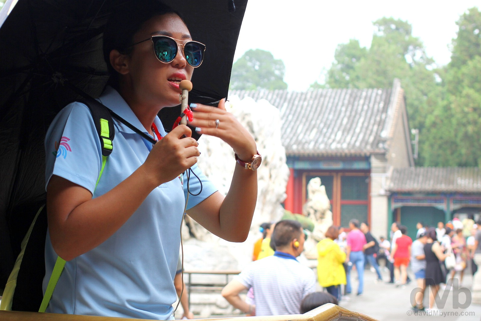 A tour guide in the grounds of the Summer Palace, Beijing, China. August 11, 2017.